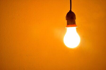 Gloeilamp oranje licht op de muur