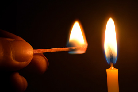 lit candles: Holding Matches and candle fire on black background Stock Photo