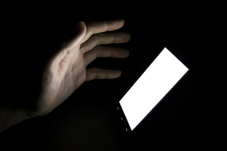 light to dark: finger touch white screen Mobile telephone in the darkroom