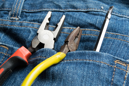 contractors: Pliers and screwdriver on bag jean background Stock Photo