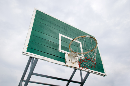 the height of a rim: Basketball Hoop  - Outdoor basketball hoop and green backboard, taken from a Bottom side view. Isolated on sky background.