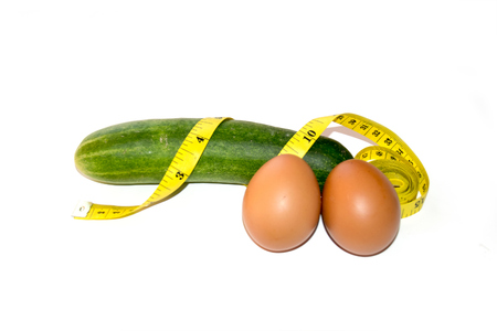 sexy funny: Like Penis - Cucumber eggs with yellow tape isolate on white Stock Photo