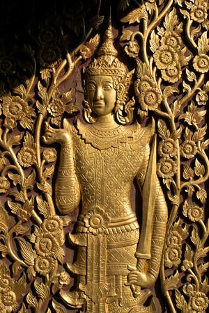 wood carving door: Gold deity hold sword sculptured wood door in temple , thailand