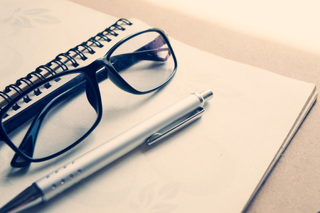 note pad and pen: Glasses and pen on notebook - Soft light vintage style