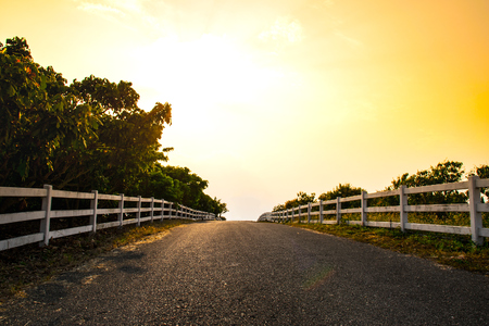 road side: White fence and road side in the evening. Stock Photo