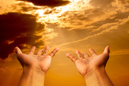 shining through: hands to pray or hope in Gold sky and sun shine heaven