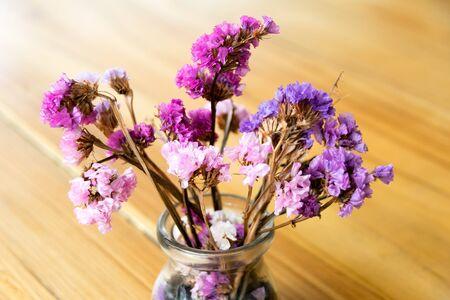 flores moradas: flores púrpuras en un florero de cristal en la mesa de madera Foto de archivo