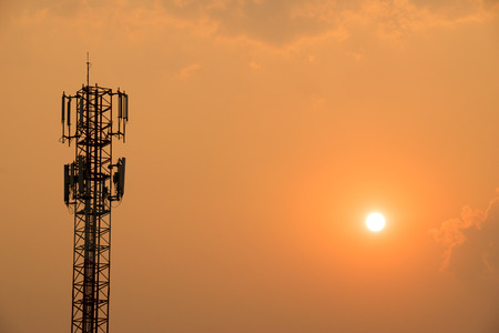 cell tower: Cell Phone Antenna Tower under orange sky and sun