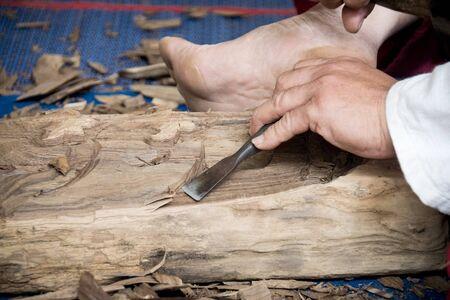 trinchante: Hombre de madera Carver está utilizando un cincel de madera para extraer.