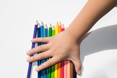 colored paper: Hand boy holding pencil colors on white future board Stock Photo
