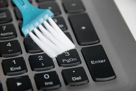 Close up blauen Pinsel hält auf Laptop-Tastatur zu reinigen Standard-Bild - 61614390