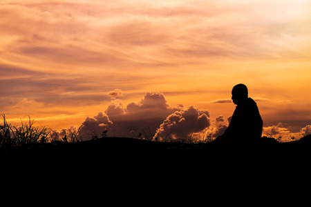 Silhouette - The Buddhist Monk Meditation and clouds evening sky Stock Photo