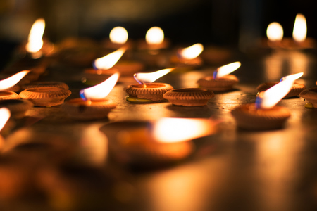 Close up Light bulbs or Lighted candle to worship the Buddha in night time Stock Photo