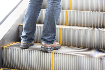 close up leg of Men wear jeans, leather shoes. Standing on the escalator