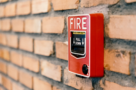 Close up fire alarm activation box on brick wall in room