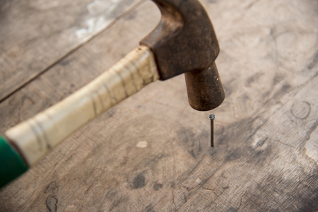 Close up hammer put nail on wooden floor