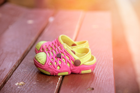 Close up pink and green Children's Sandals shoes on the table Standard-Bild