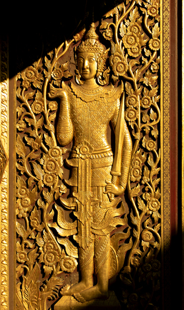 Golden thai art Culture door are Deva and flowers in the temple of Thailand isolate on white