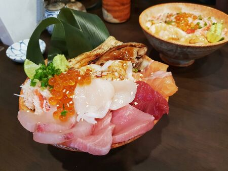Raw sashimi sushi fish on the rice bowl, typical traditional japanese dish