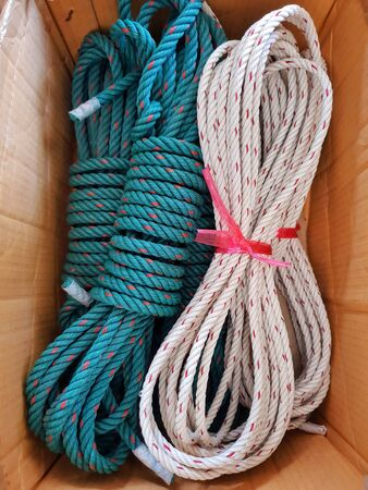 close up of rolled green and white nylon and red dot rope on a wooden background