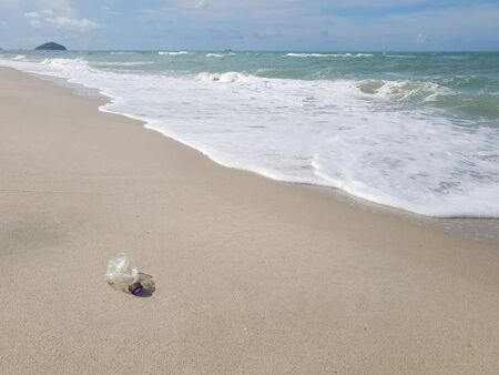 beach plastic bottle garbage with shells . Sandy beach with bubble wave