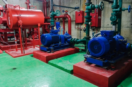Electrical water pump driven motor with green pipes in pump room