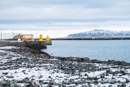Beautiful view of Iceland winter season and Yellow lighthouse tower on stone breakwater rekjavik port with snow-capped mountain in the background