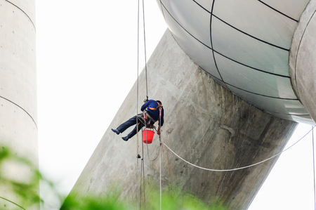 to maintain: Cleaning windows service on high rise building. The man climber or Spiderman which clean or wipe glass and exterior wall of skyscraper that it is dangerous work for Professional worker.
