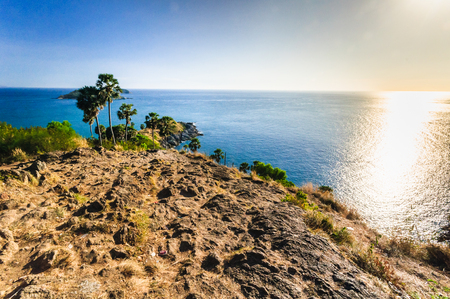 Beautiful Landscape and Tropical. Before Sunset over the sea and Cape which Coconut tree on the cape with blue sea, sky background and rock cape foreground with the sunlight reflection on the water - wide angle. Phromthep cape viewpoint at blue sky in Phu Stock Photo