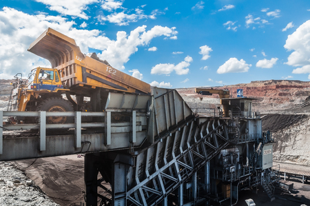 Big dump truck is mining machinery, or mining equipment to transport coal from open-pit or open-cast mine as the Coal Production. Loading of coal ore from dump truck to the crusher house. Editorial