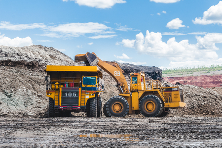 Excavator loading of coal, ore on the dump truck. The big dump truck is mining machinery, or mining equipment to transport coal from open-pit or open-cast mine as the Coal Production. Stock Photo