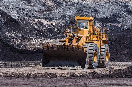 Mining Equipment or Mining Machinery, Bulldozer, wheel loader, shovels, loading of coal, ore on the dump truck from open-pit or open-cast mine as the Coal Production. Stock Photo