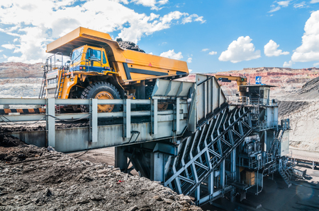 Big dump truck is mining machinery, or mining equipment to transport coal from open-pit or open-cast mine as the Coal Production. Loading of coal ore from dump truck to the crusher house. Stock Photo