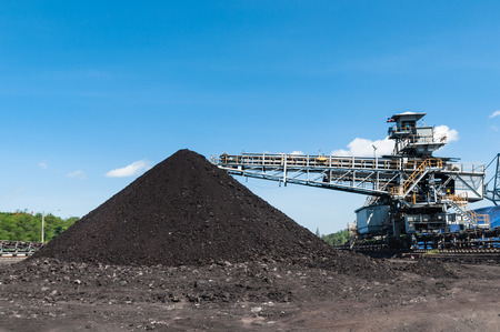 Coal Storage or Coal Stockpile for Power Plant with blue sky in the background. Stock Photo