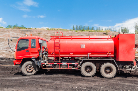 Fire engine or Fire truck in open-pit coal mine with blue sky background.