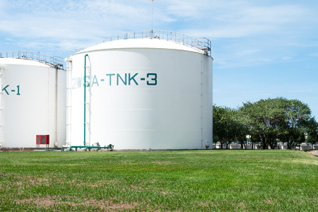 Large white industrial tanks for petrochemical or oil or fuel or water in refinery or power plant or industrail plant and green pipelines on the sideway of the tank on blue sky background.