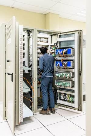 Electrician working with screwdriver or multimeter for installation, connecting, checking, wiring and fix the electrical equipment on the electrical panel in the control room, power plant Archivio Fotografico
