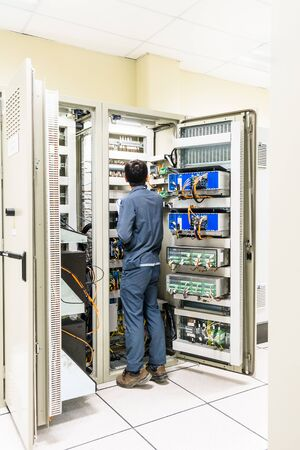 Electrician working with a screwdriver or multimeter for installation, connecting, checking, wiring and fix the electrical equipment on the electrical panel in the control room, power plant