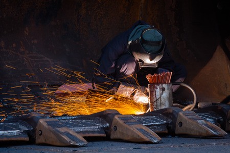Industrial Worker labourer or welder at the Manufacturing factory welding metal or steel structure. Hot Work safety or Welding safety with masks and gloves to protect lights and sparks.