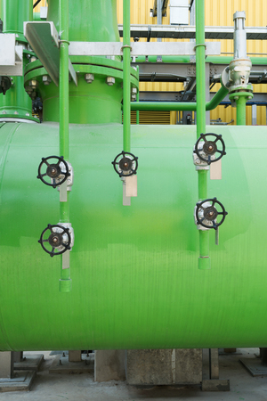 Close-up Industrial Valve contain the gas, oil or water on the pipeline. Processing Plant operates by opening, closing and isolate valve with the steel pipe and equipment on the green background. Archivio Fotografico