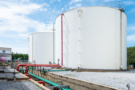 Large white industrial tanks for petrochemical or oil or fuel or water in refinery or power plant or industrail plant and red fire fighting pipelines on the side of the tank on blue sky background.