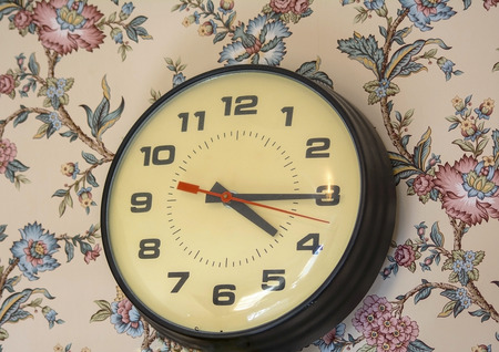 antiquated: Old analog clock resting on wall with floral wallpaper.