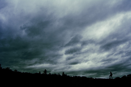 moody sky: Silhouetted Figure on Moody Sky Background Stock Photo