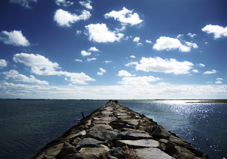 Long Rock Path through Ocean Stock Photo