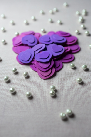 pink satin: Purple hearts and pearls lying on a beige fabric. Stock Photo