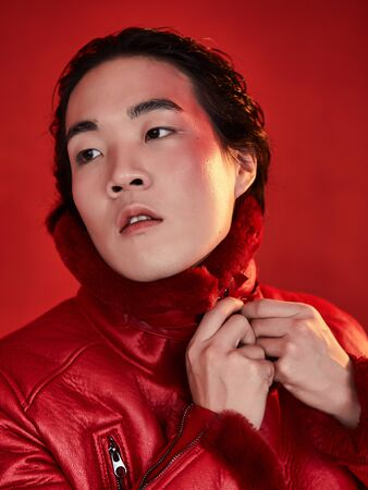Asian man in red clothes on a red background