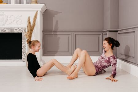 The older sister teaches yoga to the younger sister in a beautiful interior