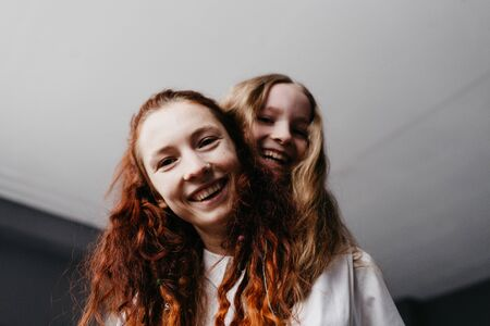 Portrait of the younger and older sisters in white shirts