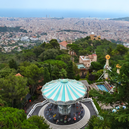 merry go round: Carousel witch tourquise roof in the trees with city view of Barcelona