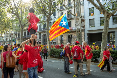 strret: BARCELONA, SPAIN - SEPT. 11: Generations on the background of people manifasteting ingependence on the strret of Barcelona during the National Day of Catalonia on Sept. 11, 2014 in Barcelona, Spain.